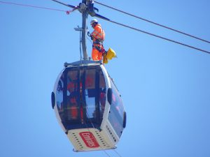 a man working at a great height on a cable car