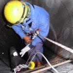 a man climbing into a confined space