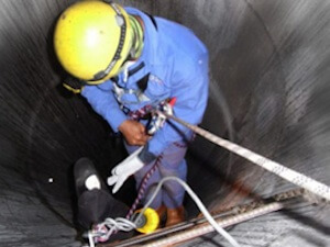 a man climbing into a confined space